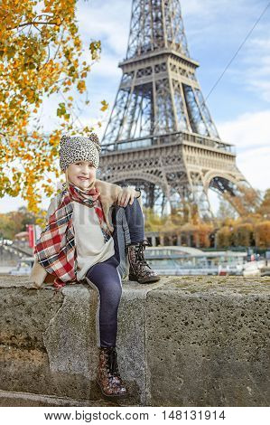 Having fun time near the world famous landmark in Paris. Portrait of happy elegant child on embankment in Paris France sitting on the parapet