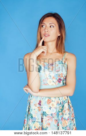 young pretty adorable woman close up like doll posing, natural makeup emotional gesturing on blue background