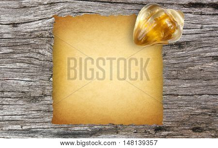 old paper with paperweight on ancient wooden desk background
