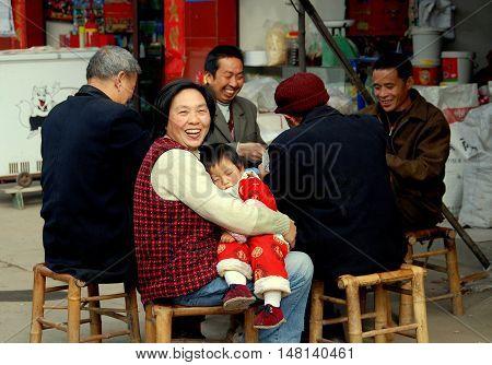 Li'an Village China - November 26 2007: Grandmother holding her grandson sitting next to four men playing cards