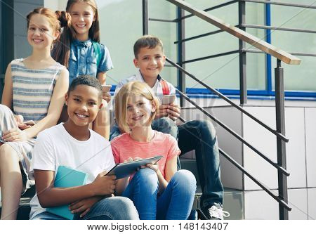 Schoolchildren with mobile phones and tablet computer sitting on school stair-steps