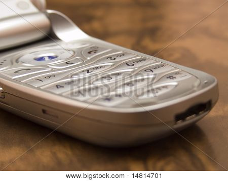 silver cellphone on wooden table