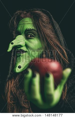 Evil Witch Holding A Red Apple