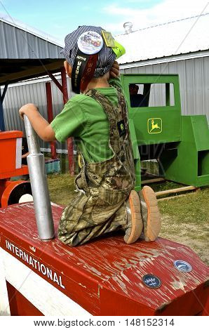ROLLAG, MINNESOTA, Sept 1. 2016: An unidentified young boy plays on the wood International tractor at the West Central Steam Threshers Reunion in Rollag, MN attended by 1000's held annually on Labor Day weekend.