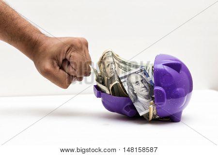 A wielded hand braking a piggy bank
