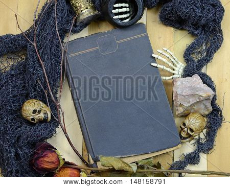 Halloween image of overhead perspective of an old book surrounded by artifacts like skulls dead flowers minerals twigs and skeleton hands. Copy space on book cover. All on a wooden table.