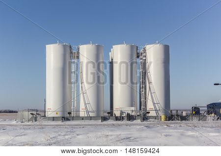 tall white storage tanks for fuel in winter