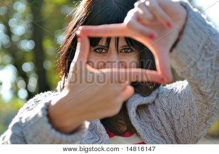 Cute young woman pretending to see the world through a lens