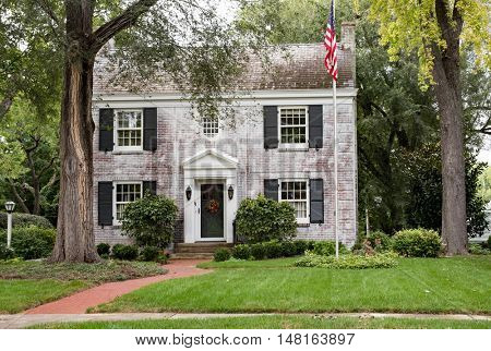 White Brick Georgian Colonial House with Flagpole