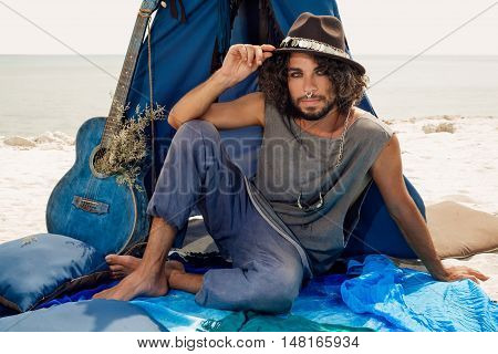 Attractive young gypsy man with guitar sitting on pillows at tepee on sea shore