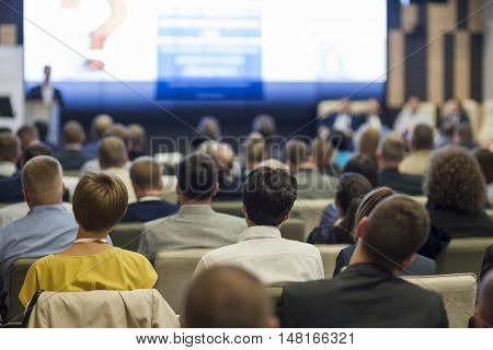 Business People Concept and Ideas. Large Group of People at the Conference Watching Presentation Charts on Screen in Front of Them. Horizontal Image