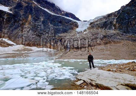 Man ecologist by moraine lake with icebergs. Angel Glacier at Mount Edith Cavell. Jasper National Park. Canadian Rockies. Alberta. Canada.