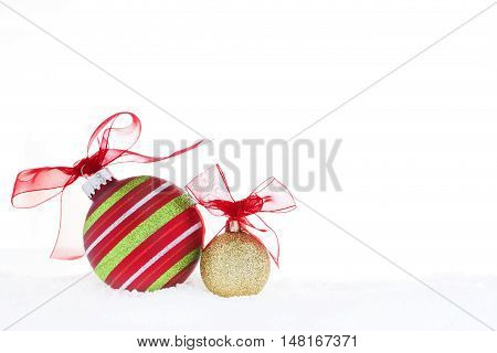 Christmas red and gold balls with red ribbon placed on the snow. Christmas decoration creative still life photography.