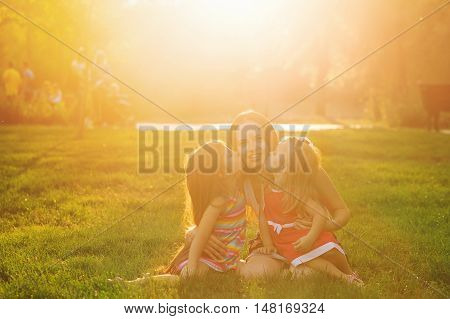 Mother and two daughters sitting on the lawn. Mother embraces daughters and they kissed her. Family time together. Cheerful picnic.