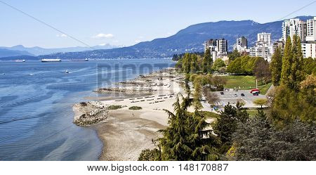 Wide view of Vancouver's English Bay and Sunset Beach Park with it many appartments and condominiums in the upper left. Shot from the Burrard Bridge with the Rockies rising majectically in the background on a gorgeous sunny day with blue skies