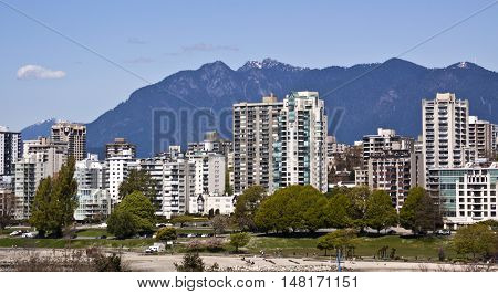 Straight on front shot of the multitude of appartments and condominiums that line Sunset Beach Park, a the popular beach in Vancouver. Shot from the Burrard Bridge with the Rockies rising majectically in the background on a gorgeous sunny day