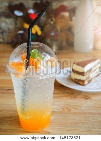 Tiramisu cake and Glass of orange soda on wooden table in coffee shop