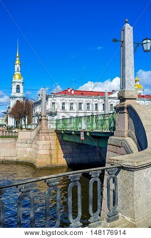 The Pikalov bridge over Griboedov Canal with the tall spire of the Naval Cathedral of St Nicholas (Sailors' Cathedral) on the background St Petersburg Russia.