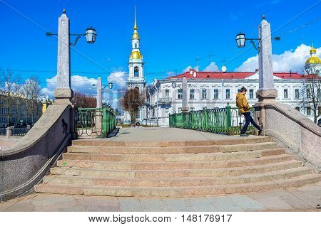 ST PETERSBURG RUSSIA - APRIL 25 2015: The stairs to the Pikalov bridge over Griboedov Canal with the Baroque Naval Cathedral of St Nicholas (Sailors' Cathedral) in front on April 25 in St Petersburg.