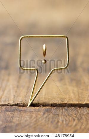 Golden speech bubble with an exclamation mark. Speech bubble made of gold wire on rustic grunge wood. Shallow depth of field.