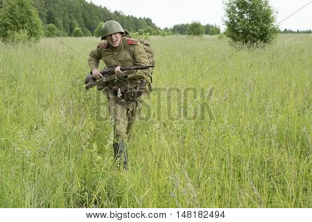 Soldier with a rifle in the field. Reconstruction of the War of 1941-1945