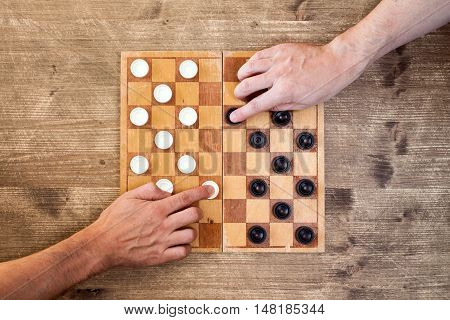 Two players starting play draughts checkers board game