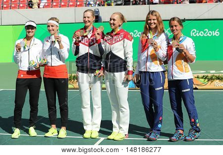 RIO DE JANEIRO, BRAZIL - AUGUST 14, 2016:Tennis women's doubles medalists team Switzerland (L), team Russia and team Czech during medal ceremony of the Rio 2016 Olympic Games at Olympics Tennis Centre
