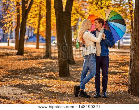 Young couple kissing in yellow autumn park . Loving couple kissing in sun in autumn park. Yellow foliage in autumn park.