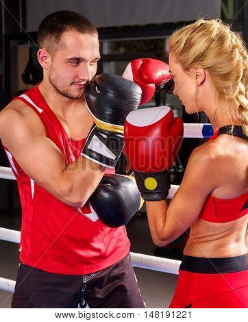 Couple man and woman wearing gloves boxing in ring. Close up of boxing couple in sport .
