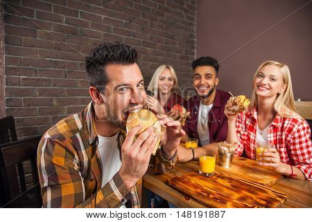 People Group Eating Fast Food Burgers Sitting At Wooden Table In Cafe, Friends Meeting Communication