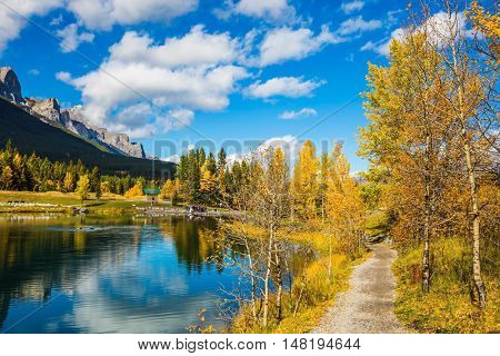 The path and yellowing aspens surround the lake. The concept of hiking. Bright shining autumn day in Canmore, near Banff National Park