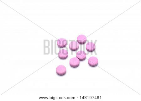 Group of pink pills isolated on white background. Tablets of drug for asthma treatment.