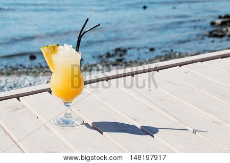 appetizing cocktail with pineapple on a background of water