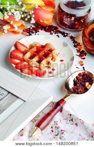 Viennese wafers with strawberry syrup and strawberries in a still life with tulips