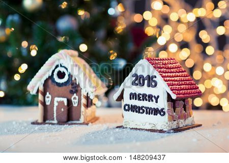 holidays, christmas, baking and sweets concept - closeup of beautiful gingerbread houses on table over lights background