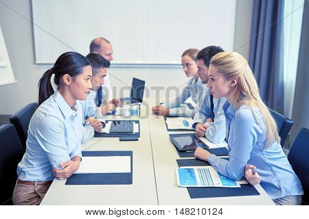 business, people, crisis and confrontation concept - smiling business team sitting on opposite sides in office