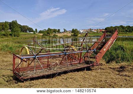 ROLLAG, MINNESOTA, Sept 1. 2016: A vintage McCormick small grain swather is displayed at the West Central Steam Threshers Reunion in Rollag, MN attended by 1000's held annually on Labor Day weekend.