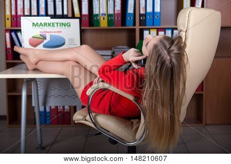 Young Business Woman talking on Telephone at Office lying in Executive Class Leather Chair putting her sexy feet up Table Computer Marketing Chart