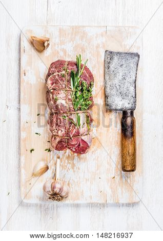 Raw uncooked roastbeef meat cut with rosemary, thyme and garlic and butcher knife on old white painted wooden background, top view, vertical composition