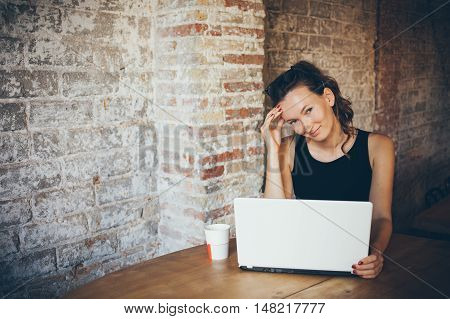 Attractive young woman is working on the laptop while sitting in a loft cafe. Brick wall is on the background. Woman is doing her favorite job on a computer. Feelling happy with favorite job. Freelancer distant job