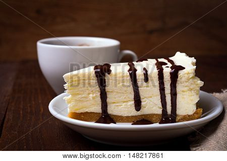 slice of cheesecake with coffee on dark background. cup of coffee and a dessert on plate