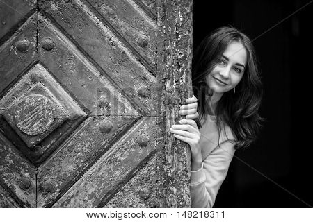 Pretty young girl peering from behind ancient wooden door, black-and-white photo.