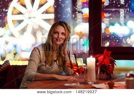 Young beautiful woman drinking champagne cocktail after work in an indoor cafe and restaurant in Paris, France. Christmas market with ferris wheel and lights on background. Happy girl dreaming on evening or night.