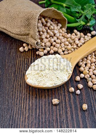 Flour chickpeas in spoonful, chick-peas in a sack and fresh green pea pods on a background of wooden boards