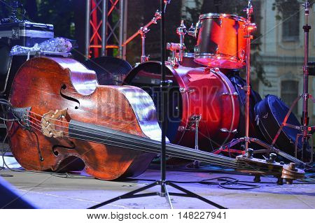 Old contrabass and drums on stage with color light