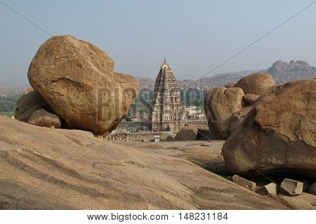 Scene in Hampi India. Virupaksha Temple and big granite boulder. UNESCO world heritage site in Karnataka. Ancient town.