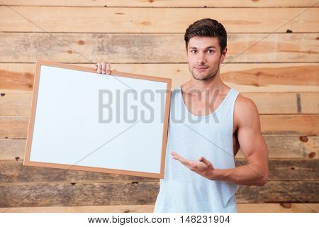 Cheerful man holding blank board and poiting on it over wooden background and looking at camera