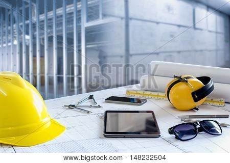 Desk of civil engineer. Working with blueprint and safety equipment against building construction.