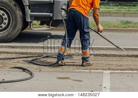 Unidentifiable road maintenance worker repairing driveway road construction works