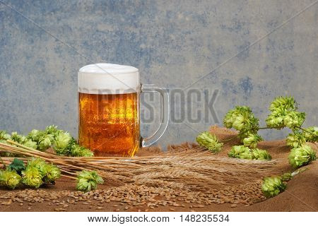 still life with glass of beer and raw material for beer production